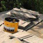 A bucket of asphalt roofing cement over a pile of roof tiles.