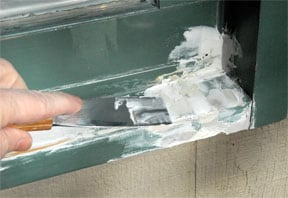 Man's hand applying vinyl compound on window sill using a putty knife.