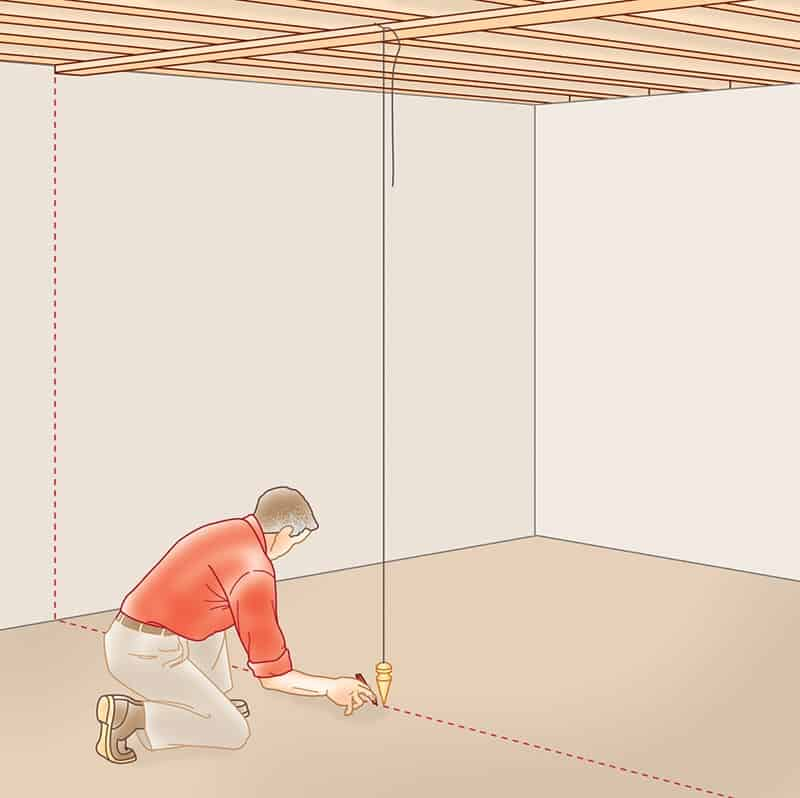 A man marking the floor below the line-up point of a hanging plumb bob.