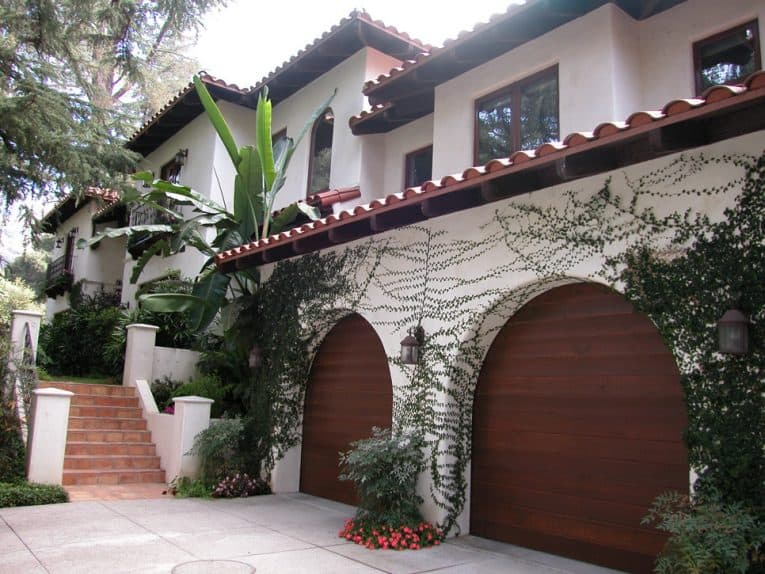 Two-story contemporary Mediterranean house's front yard including a growing vine on an archway with a wooden double door garage.