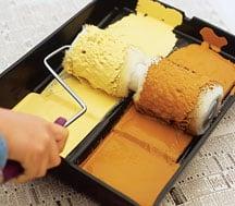 Man's hand, loading a two-part roller with paint on a dual tray.