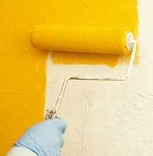 Man's hand painting a wall with yellow using a roller.
