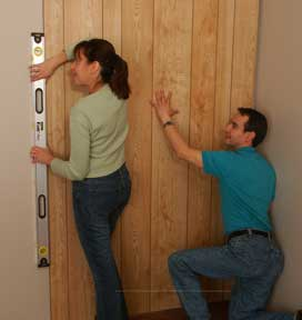 Man installing a wooden wall panel, including a woman doing spirit leveling.