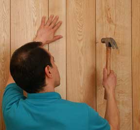 Man nailing a wooden wall panel.