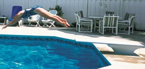 person diving off of swimming pool jump board