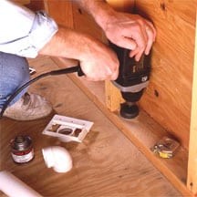 Man's hands using a power drill to bore a hole at a wall's bottom plate.