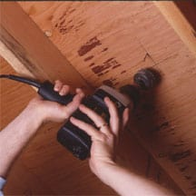 Man's hands drilling underneath the floor using a hole saw.