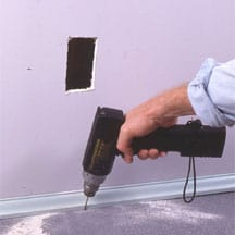 Man's hand drilling a small hole below a wall inlet opening.