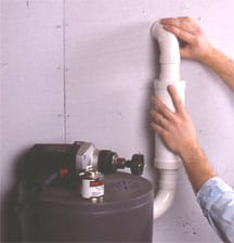 Man's hands connecting a pipe from vacuum power unit through a wall.