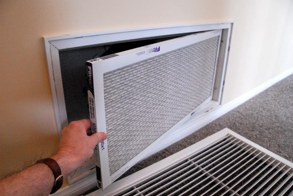 A hand placing a new air filter in a wall register, with airflow arrows pointing toward the ductwork.