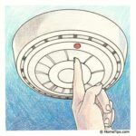 Illustration of a finger pressing the red button on a ceiling-mounted smoke detector.