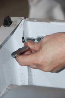 Man's hand unscrewing a clothes dryer's front lower kick plate panel.