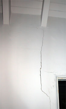 Cracked white plaster wall from a door jam extending to the ceiling.