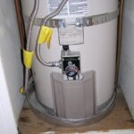 A water heater drip pan installed beneath a storage water heater.