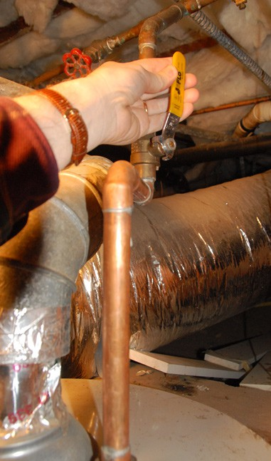 Hand demonstrating the location of a lever valve above a water heater