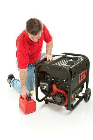 Man holding a small portable fuel tank beside an emergency generator.
