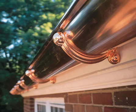 Half-round sophisticated copper rain gutter with brackets in a house's roof.