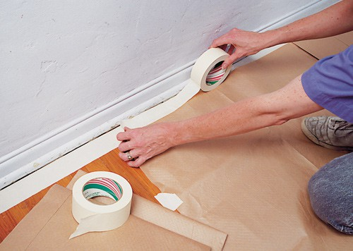 Woman's hands, securing a drop cloth along baseboards with a wide masking tape.
