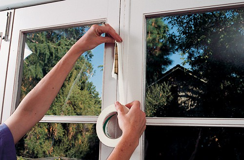 Woman's hands covering a window hinge using a masking tape.