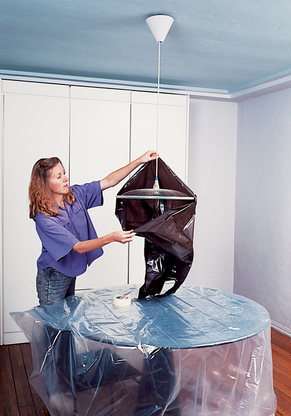 Woman covering a pendant light with a garbage bag.