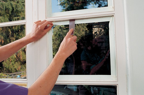 Woman's hands sealing a window pane's masked corner using a putty knife.