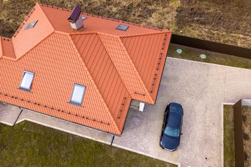 Aerial view of a terracotta style metal roof on a house.