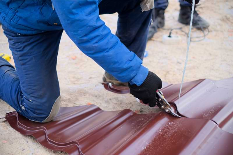 A worker cutting a piece of brown metal roofing with hand sheers.
