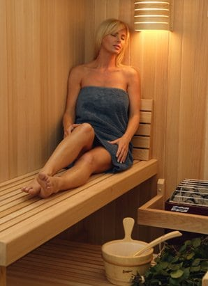 Woman sitting on a wooden bench, inside a prebuilt sauna.
