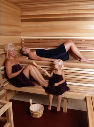 Two women and a child inside a 2-level bench precut sauna kit.
