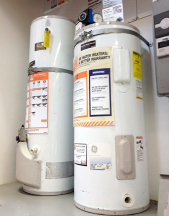 Two tanks of white cylindrical storage water heaters.