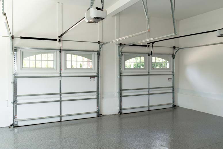 Inside a white garage room with arch stockton windows including overhead torsion springs and electric operators on two garage doors.