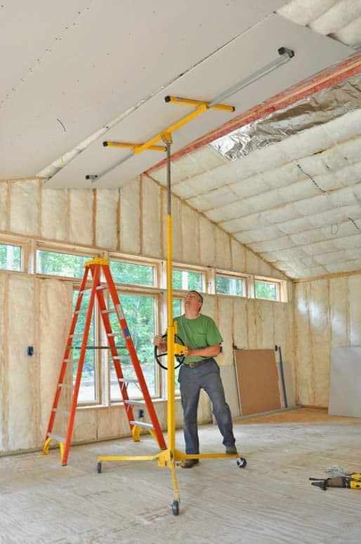 Man installing a dry wall on insulated ceiling panels using a lift.