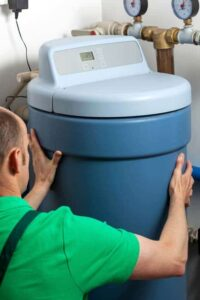Man connecting a blue water softener to a house's hot-water supply plumbing.