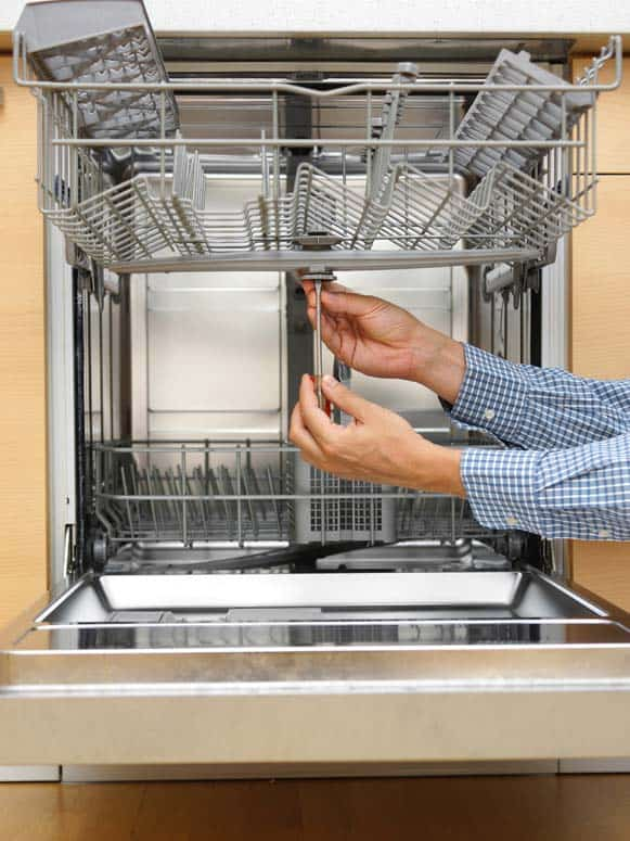 Man's hand screwing a bolt beneath a dishwasher's upper spray arm.