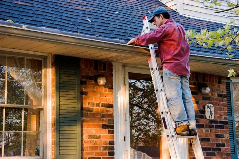 Man working on a house's rain gutter using a step ladder.