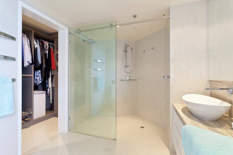 Custom glass shower doors glide along a top track. These doors provide an elegant, almost transparent barrier between room and shower.