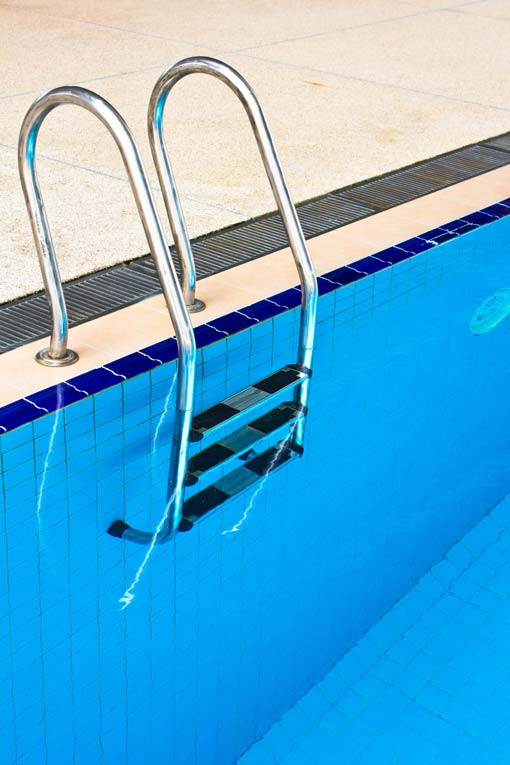 swimming pool ladder mounted at edge of pool