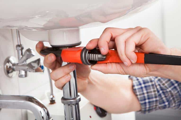 A sink is connected to the drain plumbing by a tailpiece that's tightened to the drain flange.