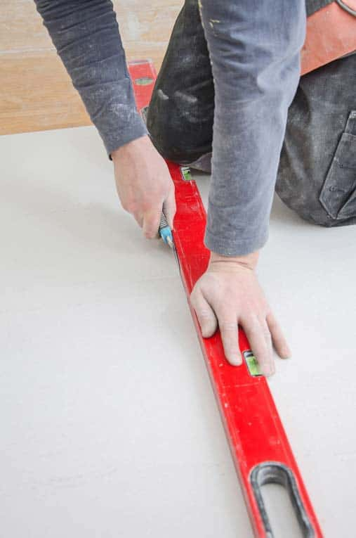 Cut drywall by slicing through the surface paper with a sharp utility knife, drawing the knife along a straightedge. Snap the piece away from the cut, and then slice through the paper backing.