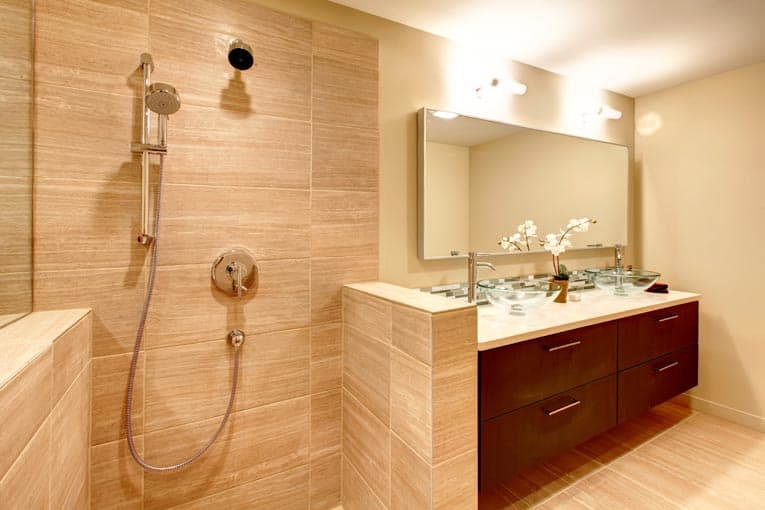 Wall-mounted cabinets contrast beautifully with this stone shower.