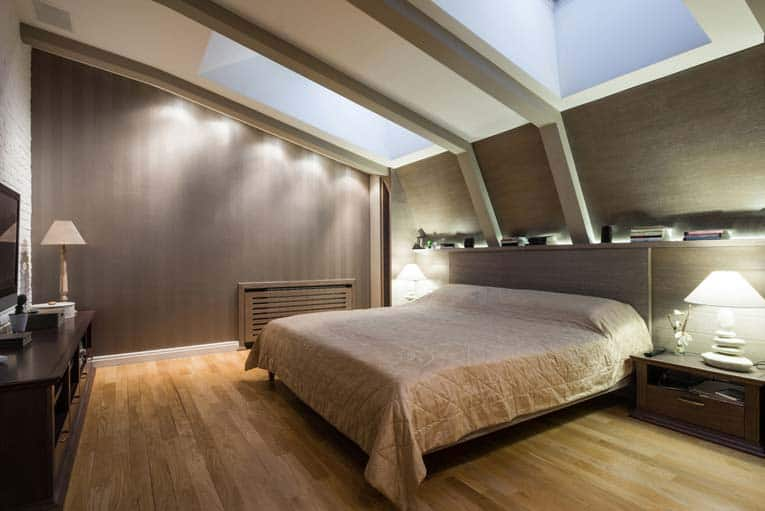 An attic bedroom with large dual skylights.
