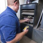 Technician in a blue shirt working on an open furnace