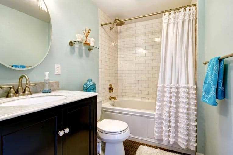A conventional small bathroom with a white alcove tub shower.