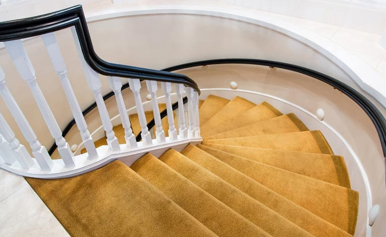 Carpeted circular stair sweeps from one floor to another, providing elegant passage.