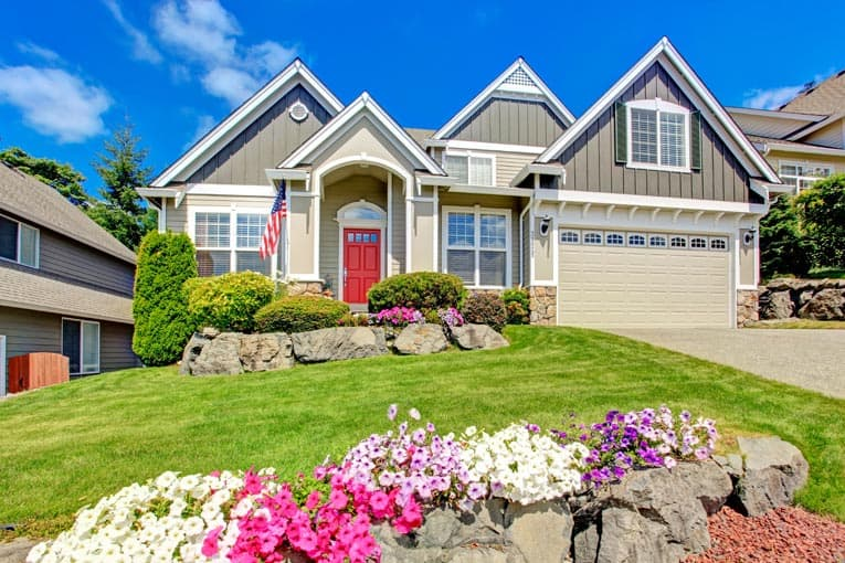 great curb appeal house with lawn flowers door