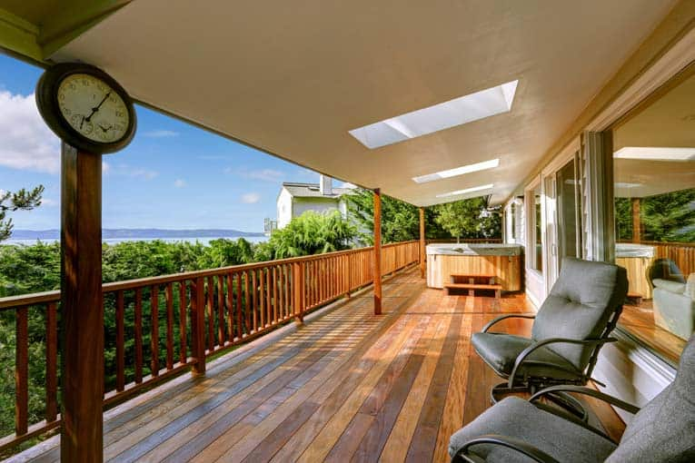 A covered wooden deck, brightening a veranda with 3 skylights.