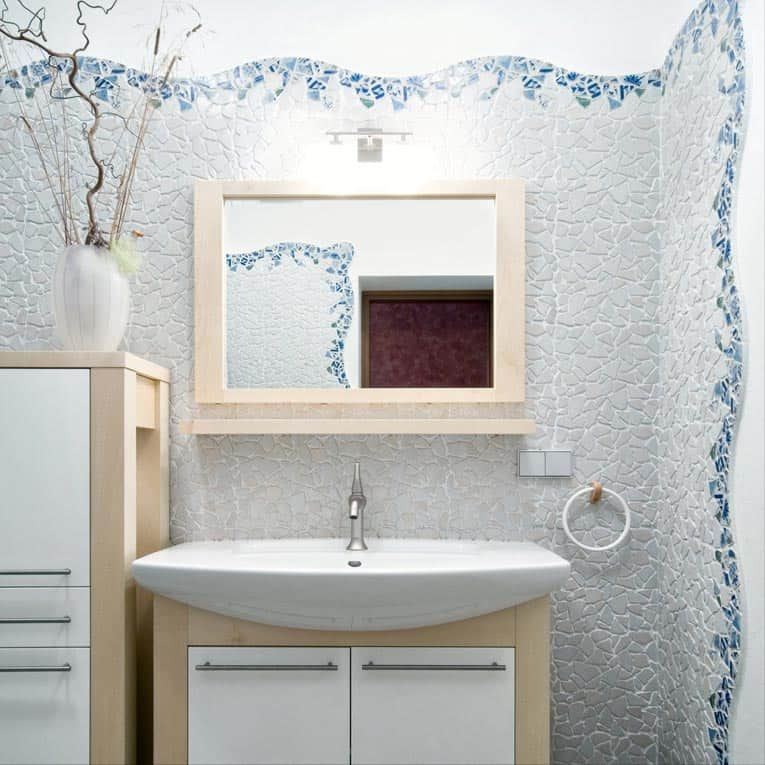 Decorative mosaic walls give this powder room artistic charm.