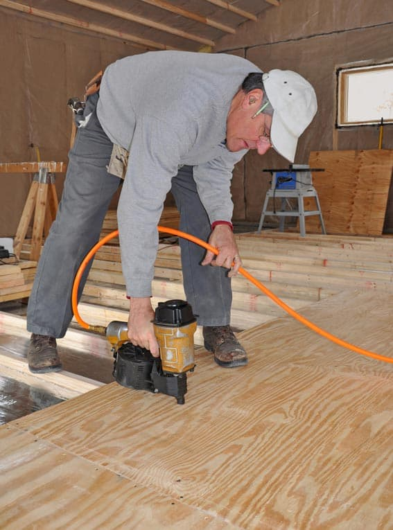 A man securing plywood as subflooring using an electric nail gun.