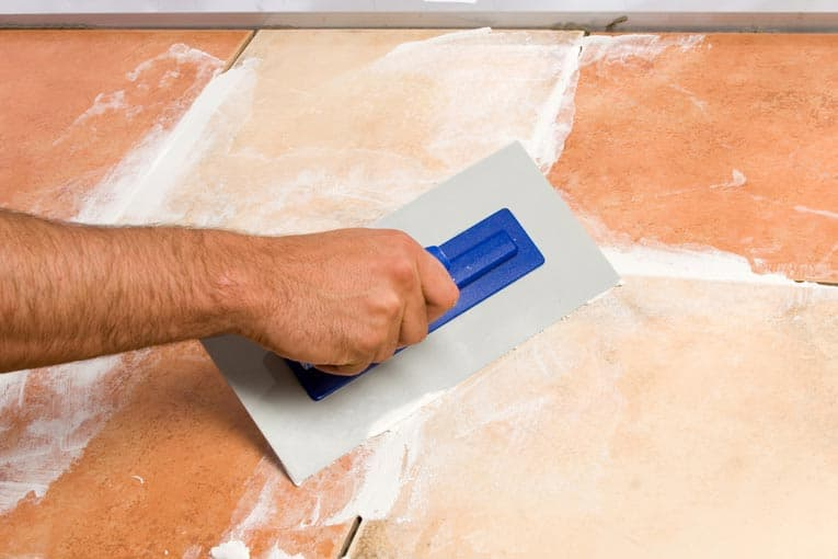 Man's hand applying grout to joints between tiles, using a grout float.
