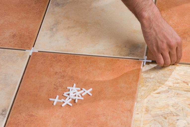 hands installing stone floor tiles, placing cross-shaped plastic spacers in grout joints to keep regular spaces between the tiles before grout is added